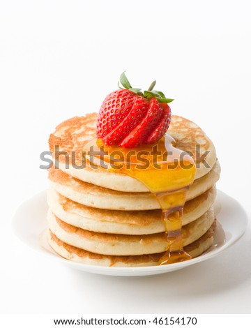 Plate of pancakes with maple syrup topped with sliced strawberry