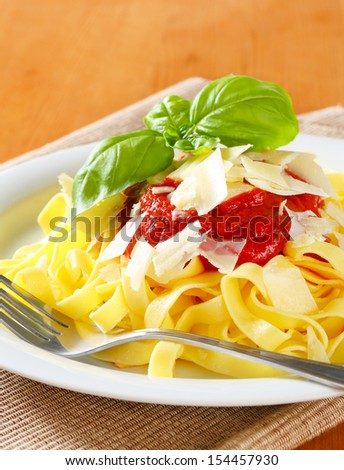 plate of pasta with ketchup sauce and parmesan on a table