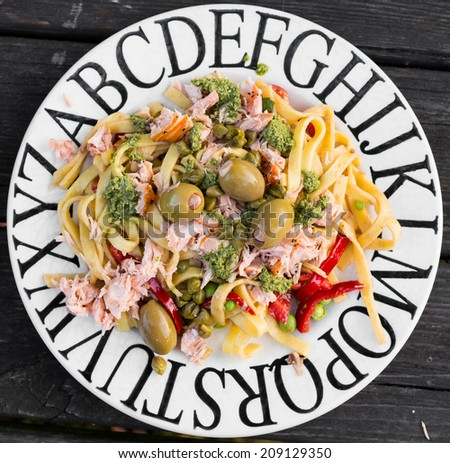 Plate of pasta with salmon and big green olives - stock photo