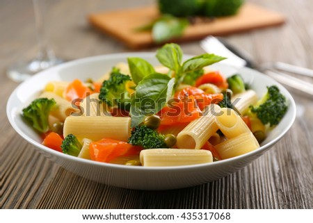 Plate of pasta with salmon and broccoli on table closeup - stock photo