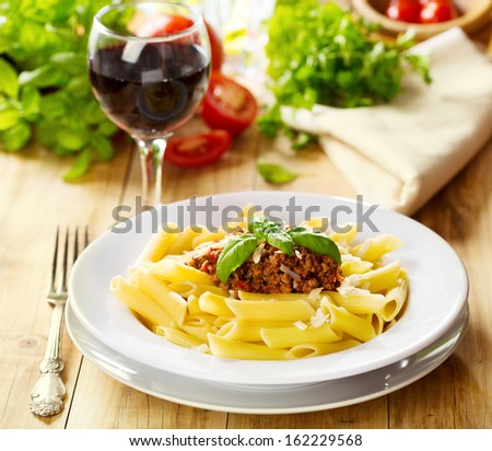 plate of penne pasta with bolognese sauce on wooden table