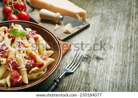 Plate of penne pasta with tomato sauce and parmesan cheese