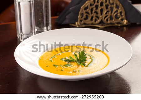 Plate of pumpkin cream soup isolated on wooden table at restaurant - stock photo