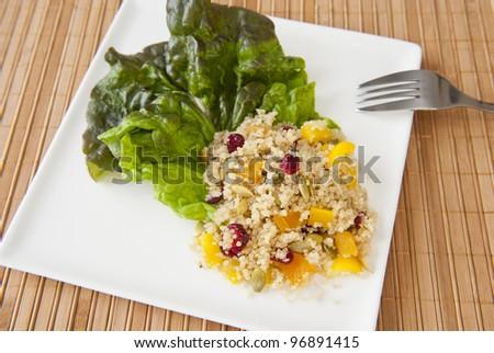 Plate of quinoa salad on a bamboo matt - stock photo