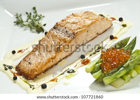 Plate of red roasted salmon served with red caviar and asparagus. - stock photo