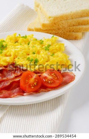 plate of scrambled eggs and fried bacon and slices of bread on white place mat - stock photo