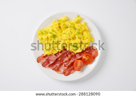 plate of scrambled eggs and slices of fried bacon on white background - stock photo