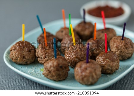 Plate of seasoned beef meatballs for appetizers with colorful toothpicks and a tangy savory dip - stock photo