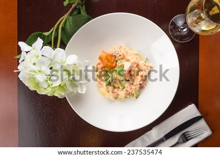 Plate of shrimp risotto with white wine and flowers on wooden table - stock photo