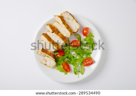 plate of sliced chicken breasts with rucola and cherry tomatoes on white background - stock photo