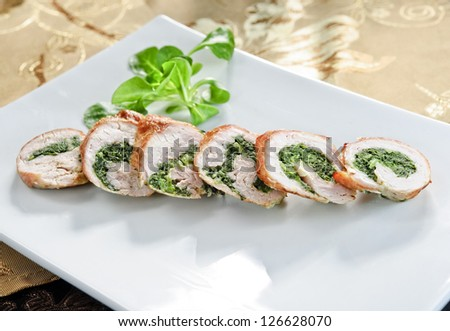 Plate of sliced chicken roll stuffed with backed spinach..
