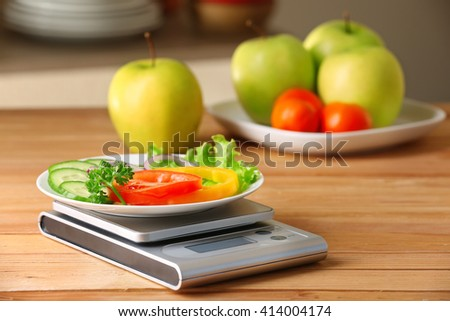 Plate of sliced fresh vegetables and digital kitchen scales on wooden table - stock photo