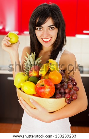 Plate of sliced fruits held by a smiling healthy girl.