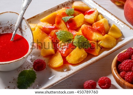 Plate of Sliced Peaches with Raspberry Sauce and Mint Leaf, selective focus.