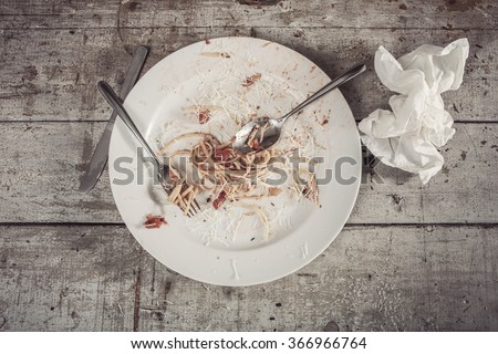 Plate of spaghetti at the end of a meal on a wooden table - stock photo