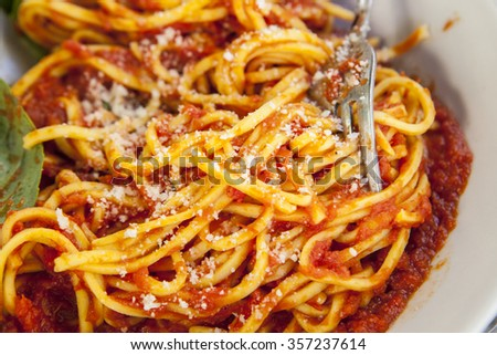 Plate of spaghetti bolognese with fork. Closeup shot selective focus - stock photo