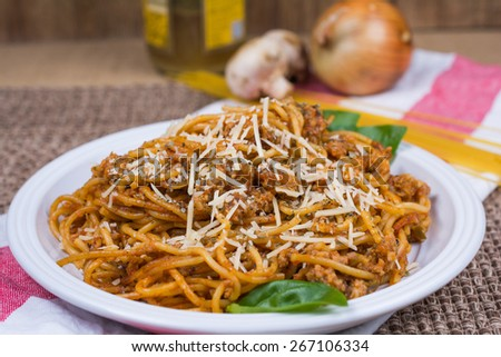 Plate of spaghetti garnished with fresh basil leaves and grated parmesan cheese. Background has onions, olive oil and mushroom. - stock photo
