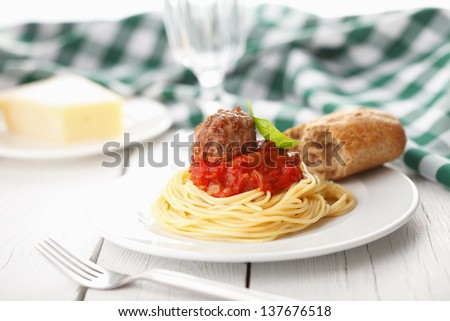 Plate of spaghetti with meatballs in tomato marinara sauce and ingredients on white wooden table - stock photo
