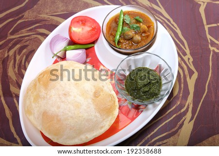 plate of spicy chole bhature, with green chili topping and chutney indian dish