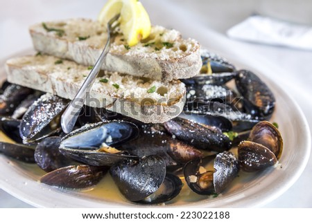 Plate of steamed mussels in sauce with bread, cheese and lemon