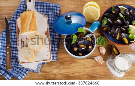 Plate of steamed mussels on a wooden background. View from above - stock photo