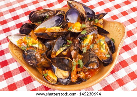 Plate of steamed mussels with tomato and white wine sauce, marinara sauce - stock photo
