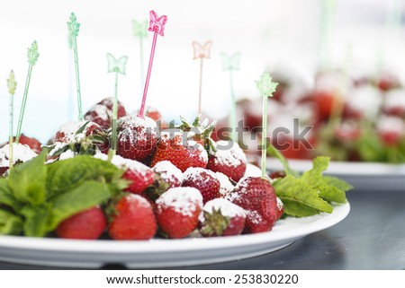 plate of succulent juicy fresh ripe red strawberrie on multicolored plastic food skewers in butterfly and leaf shape decorated with mint - stock photo