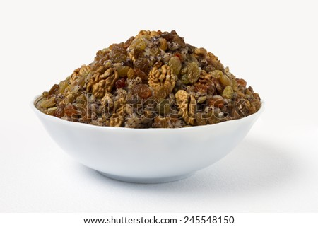 Plate of sweet porridge with raisins, nuts and poppy seeds on a white background. Kutia. - stock photo