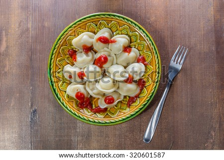plate of the pelmeni seasoned with ketchup and a fork