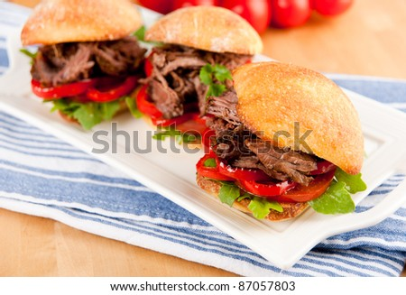 Plate of Three Tiny Slider Sandwiches with Pulled Beef and Red Bell Peppers - stock photo