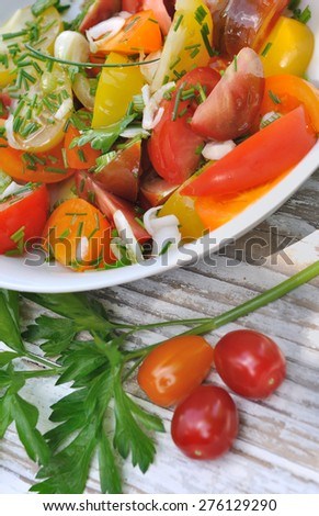 plate of tomatoes and aromatics herbs on wooden table  - stock photo