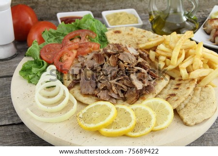 Plate of traditional Greek gyros with meat, fried potatoes, tomato and onion - stock photo