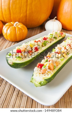 Plate of two quinoa salad stuffed zuchinis with fall pumpkins - stock photo