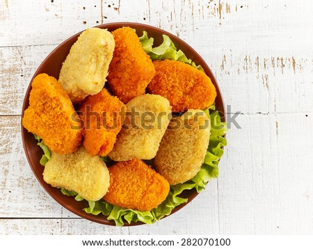 plate of various chicken nuggets on white wooden table, top view - stock photo