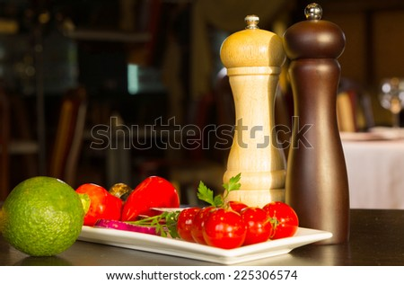 Plate of vegetables with red bell peppers, onion rings and ripe cherry tomatoes with salt and pepper condiments in mills on a dinner table - stock photo