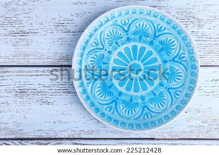 Plate on color wooden background - stock photo