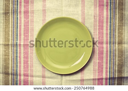 plate on linen napkin in vintage style - stock photo