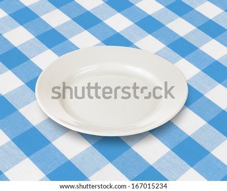 plate or dish over blue checked fabric tablecloth - stock photo
