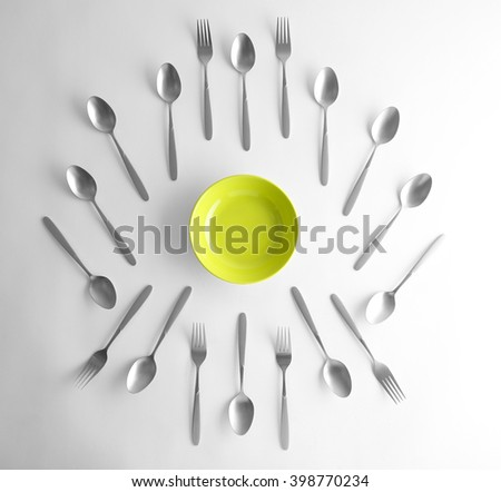 Plate, silver spoons and forks, top view - stock photo