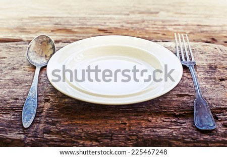 Plate, spoon and fork on old rustic wooden table - stock photo