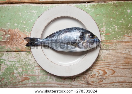 Plate with a fresh fish (Sparus aurata) on rustic green table - stock photo