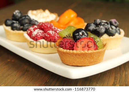 Plate with a nice assortment of fresh fruity tart - stock photo