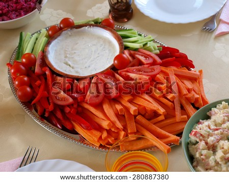Plate with appetizers - sliced vegetables and sauce on the party table          - stock photo