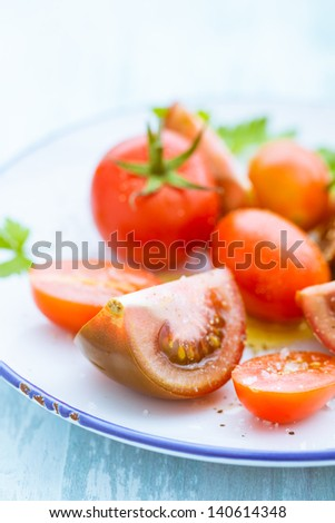 Plate with assorted tomatoes with focus to a quartered sliced tomato in the foreground - stock photo