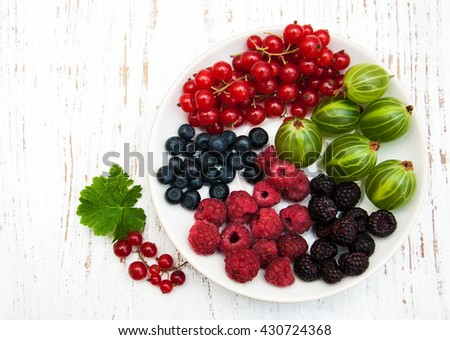 plate with berries on old wooden background