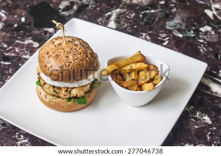 Plate with chicken burger with camembert cheese and a small glass with fries - stock photo
