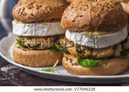 Plate with chicken burgers with camembert cheese