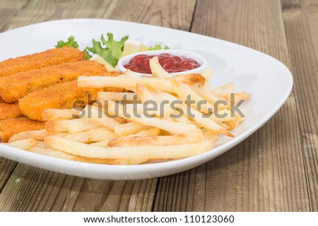 Plate with Chips and Fish Fingers on wooden background