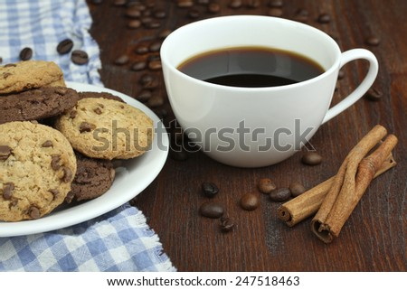 Plate with chocolate cookies and cup of hot coffee on old wooden table.