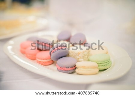 plate with colorful macaroon on table - stock photo